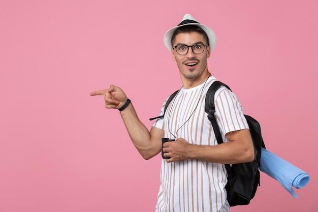 Vue de face jeune homme en t-shirt blanc avec des jumelles sur fond rose