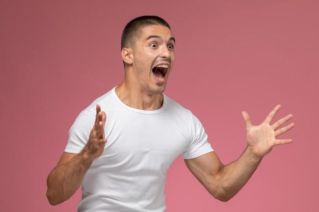 Vue de face jeune homme en t-shirt blanc posant et criant sur fond rose