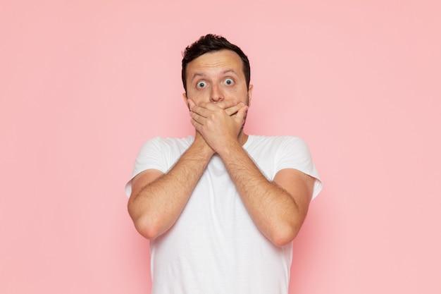 Une vue de face jeune homme en t-shirt blanc posant avec une expression choquée