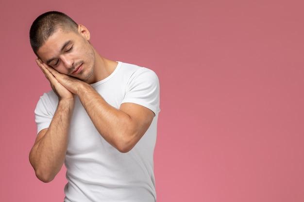 Vue de face jeune homme en t-shirt blanc posant en expression endormie sur fond rose