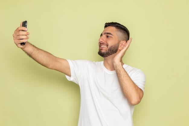 Une vue de face jeune homme en t-shirt blanc prenant un selfie avec sourire