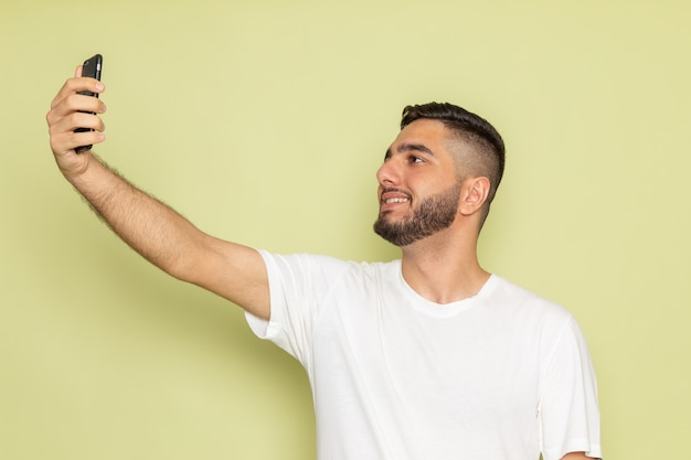 Une vue de face jeune homme en t-shirt blanc prenant un selfie