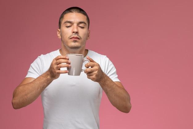 Vue de face jeune homme en t-shirt blanc sentant un parfum de café sur fond rose