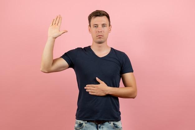 Vue de face jeune homme en t-shirt bleu posant avec une main levée sur fond rose modèle de couleur d'émotion masculine humaine