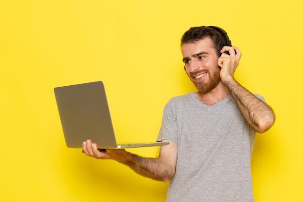 Une vue de face jeune homme en t-shirt gris à l'aide d'un ordinateur portable avec le sourire sur le modèle de couleur expression émotion homme mur jaune