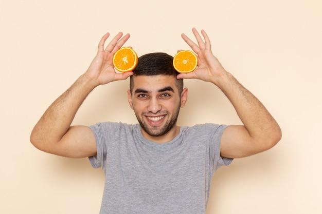 Vue de face jeune homme en t-shirt gris et jean bleu souriant et tenant des tranches d'orange sur beige