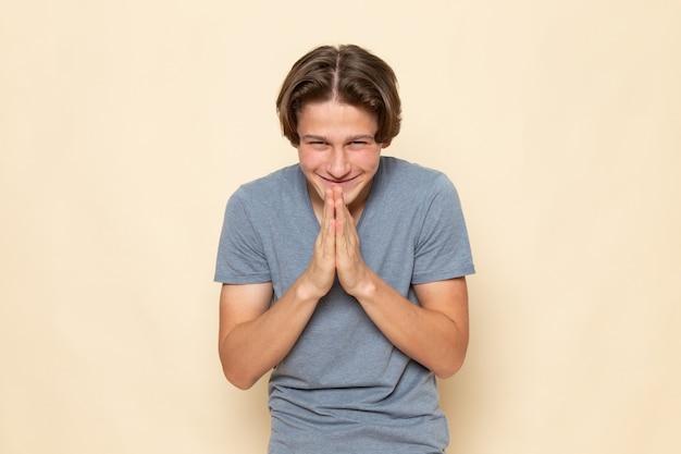 Une vue de face jeune homme en t-shirt gris posant avec une expression curieuse