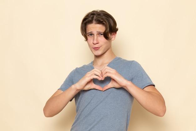 Une vue de face jeune homme en t-shirt gris posant montrant signe de coeur