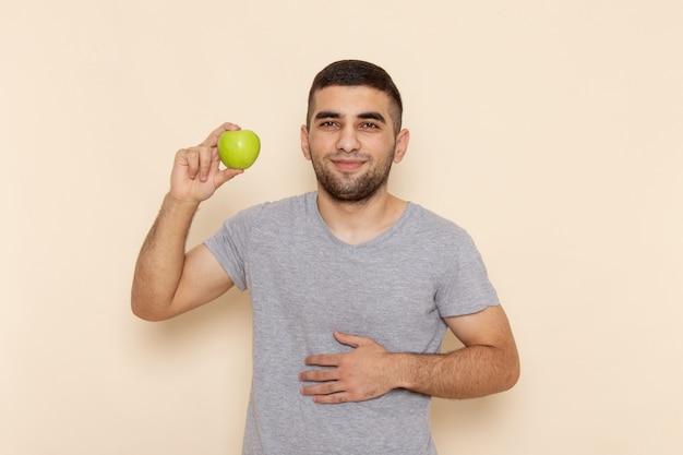 Vue de face jeune homme en t-shirt gris tenant une pomme verte sur beige