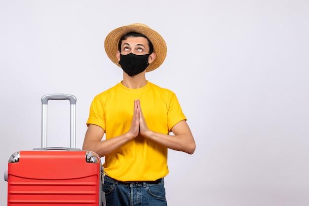 Vue de face jeune homme avec t-shirt jaune et valise rouge joignant les mains