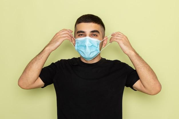 Vue de face jeune homme en t-shirt noir portant un masque stérile sur vert