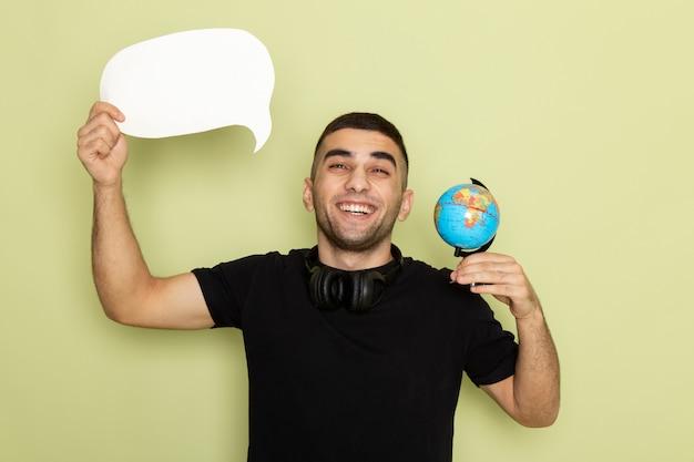 Vue de face jeune homme en t-shirt noir tenant une pancarte blanche et petit globe avec sourire sur vert