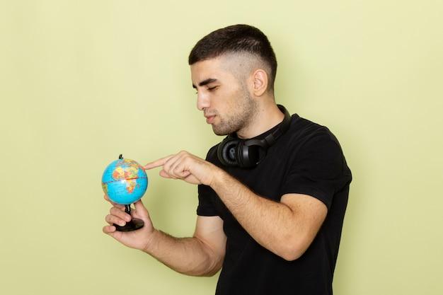 Vue de face jeune homme en t-shirt noir tenant petit globe vert