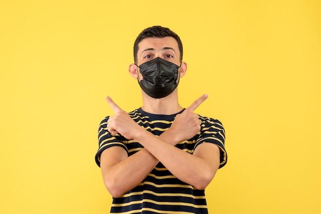 Vue de face jeune homme en t-shirt rayé noir et blanc croisant les mains sur fond isolé jaune