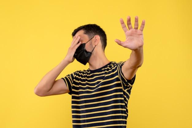 Vue de face jeune homme en t-shirt rayé noir et blanc faisant panneau d'arrêt fermant les yeux sur fond jaune