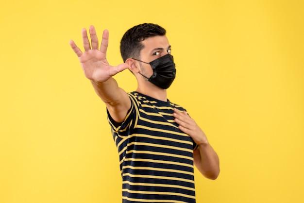 Vue de face jeune homme en t-shirt rayé noir et blanc faisant panneau d'arrêt sur fond jaune