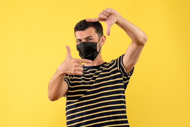 Vue de face jeune homme en t-shirt rayé noir et blanc faisant signe de caméra fond jaune