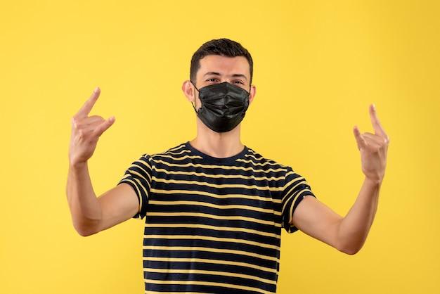 Vue de face jeune homme en t-shirt rayé noir et blanc faisant signe de roche fond jaune
