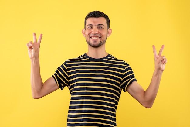 Vue de face jeune homme en t-shirt rayé noir et blanc faisant la victoire chanter sur fond isolé jaune