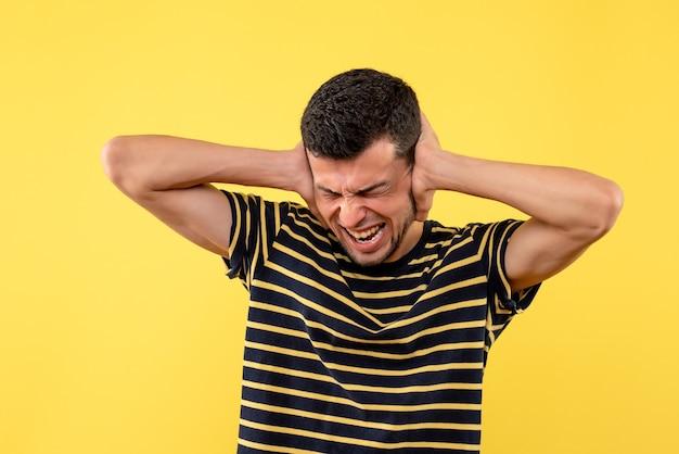 Vue de face jeune homme en t-shirt rayé noir et blanc fermant les oreilles avec les mains sur fond isolé jaune