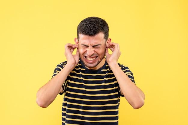 Vue de face jeune homme en t-shirt rayé noir et blanc fermant ses oreilles avec les mains sur fond isolé jaune