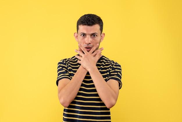 Vue de face jeune homme en t-shirt rayé noir et blanc fond isolé jaune avec espace libre