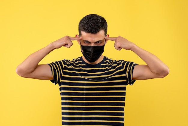 Vue de face jeune homme en t-shirt rayé noir et blanc mettant les doigts sur sa tempe sur fond jaune