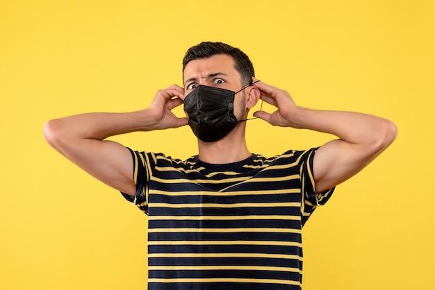 Vue de face jeune homme avec t-shirt rayé noir et blanc mettant sur fond jaune masque noir