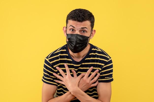 Vue de face jeune homme en t-shirt rayé noir et blanc mettant les mains sur la poitrine sur fond isolé jaune