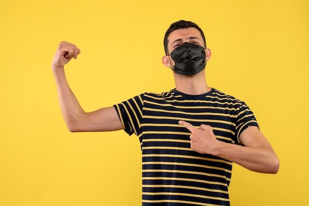 Vue de face jeune homme avec t-shirt rayé noir et blanc montrant fond jaune de muscle de bras
