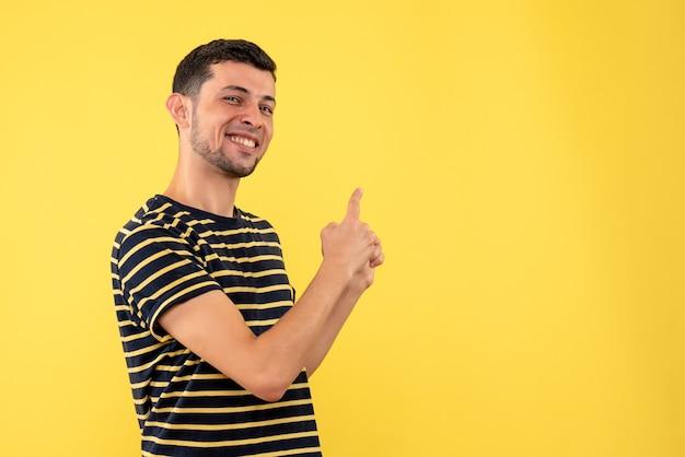 Vue de face jeune homme en t-shirt rayé noir et blanc pointant vers l'arrière sur fond isolé jaune