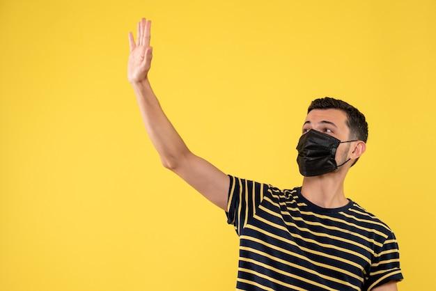 Vue de face jeune homme avec t-shirt rayé noir et blanc saluant quelqu'un fond jaune