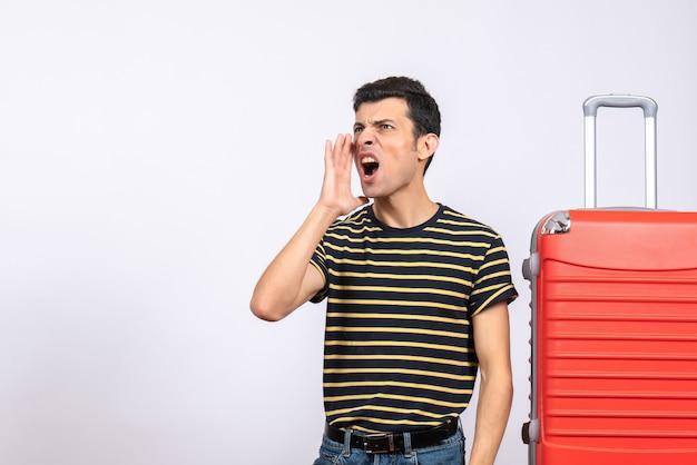 Vue de face jeune homme avec t-shirt rayé et valise appelant quelqu'un