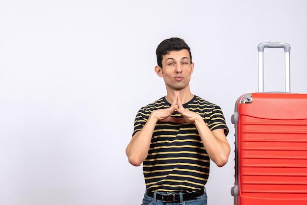 Vue de face jeune homme avec t-shirt rayé et valise joignant les mains