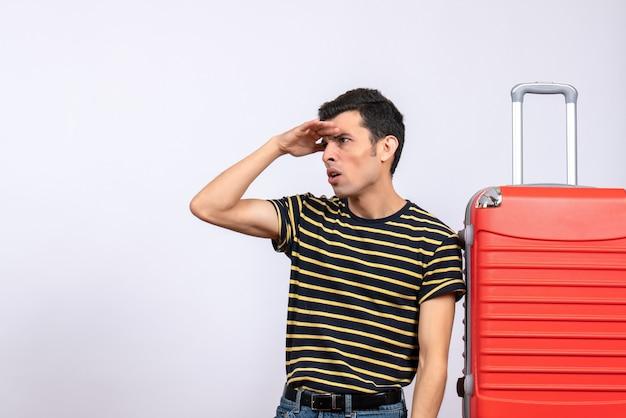 Vue de face jeune homme avec t-shirt rayé et valise rouge observation