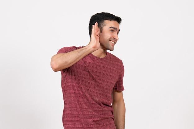 Vue de face jeune homme en t-shirt rouge foncé essayant d'entendre sur fond blanc