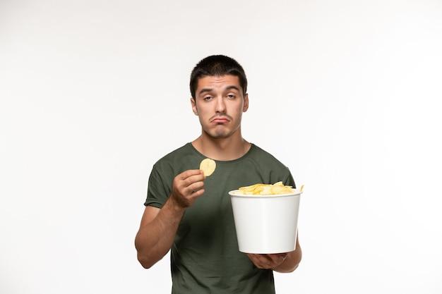 Vue de face jeune homme en t-shirt vert avec des cips de pommes de terre et de manger sur le mur blanc personne solitaire film cinéma cinéma