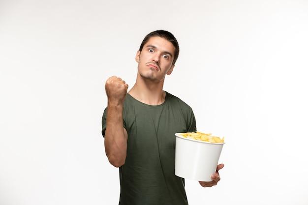 Vue de face jeune homme en t-shirt vert avec des cips de pommes de terre et menaçant sur mur blanc film cinéma films films solitaire personne