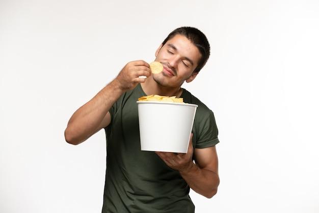 Vue de face jeune homme en t-shirt vert holding cips de pommes de terre manger sur mur blanc film film seul cinéma personne