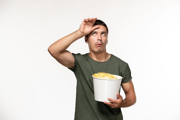 Vue de face jeune homme en t-shirt vert holding cips de pommes de terre sur mur blanc personne solitaire cinéma films films