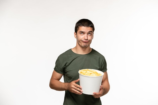 Vue de face jeune homme en t-shirt vert holding cips de pommes de terre regarder un film sur mur blanc clair personne solitaire film cinéma cinéma