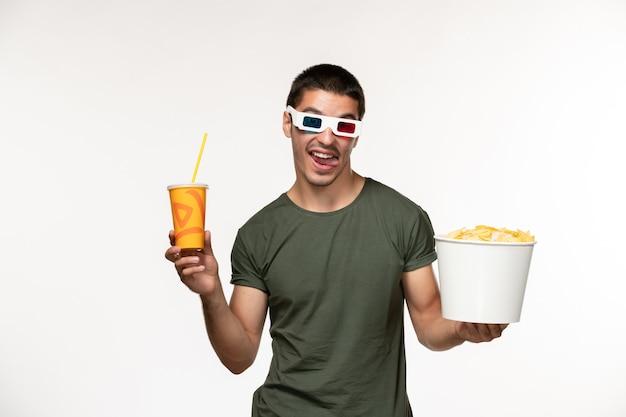 Vue de face jeune homme en t-shirt vert holding potato cips soda en d lunettes de soleil sur mur blanc film cinéma masculin solitaire
