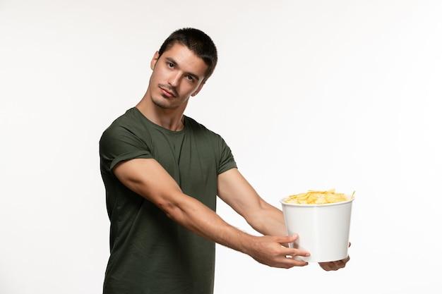 Vue de face jeune homme en t-shirt vert avec pommes de terre cips sur mur blanc personne solitaire cinéma films films