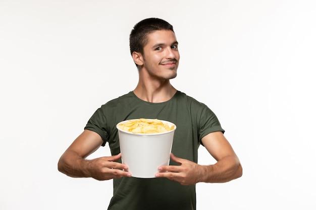 Vue de face jeune homme en t-shirt vert avec pommes de terre cips sur sol blanc personne solitaire cinéma films films