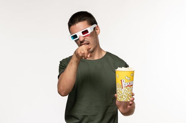 Vue de face jeune homme en t-shirt vert tenant du pop-corn dans des lunettes de soleil en regardant un film sur mur blanc film cinéma solitaire