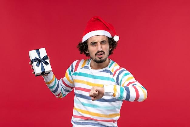 Vue de face jeune homme avec temps de contrôle présent sur le mur rouge nouvel an vacances émotion