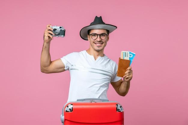 Vue de face d'un jeune homme tenant un appareil photo et des billets d'avion sur un mur rose clair