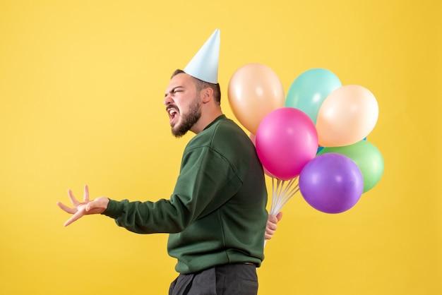 Vue de face jeune homme tenant des ballons colorés derrière son dos sur fond jaune clair
