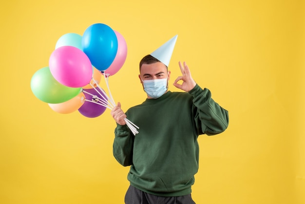 Vue de face jeune homme tenant des ballons colorés sur fond jaune