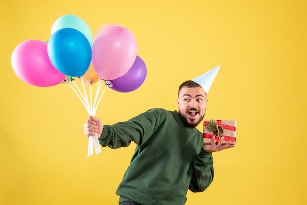Vue de face jeune homme tenant des ballons colorés et présents sur fond jaune
